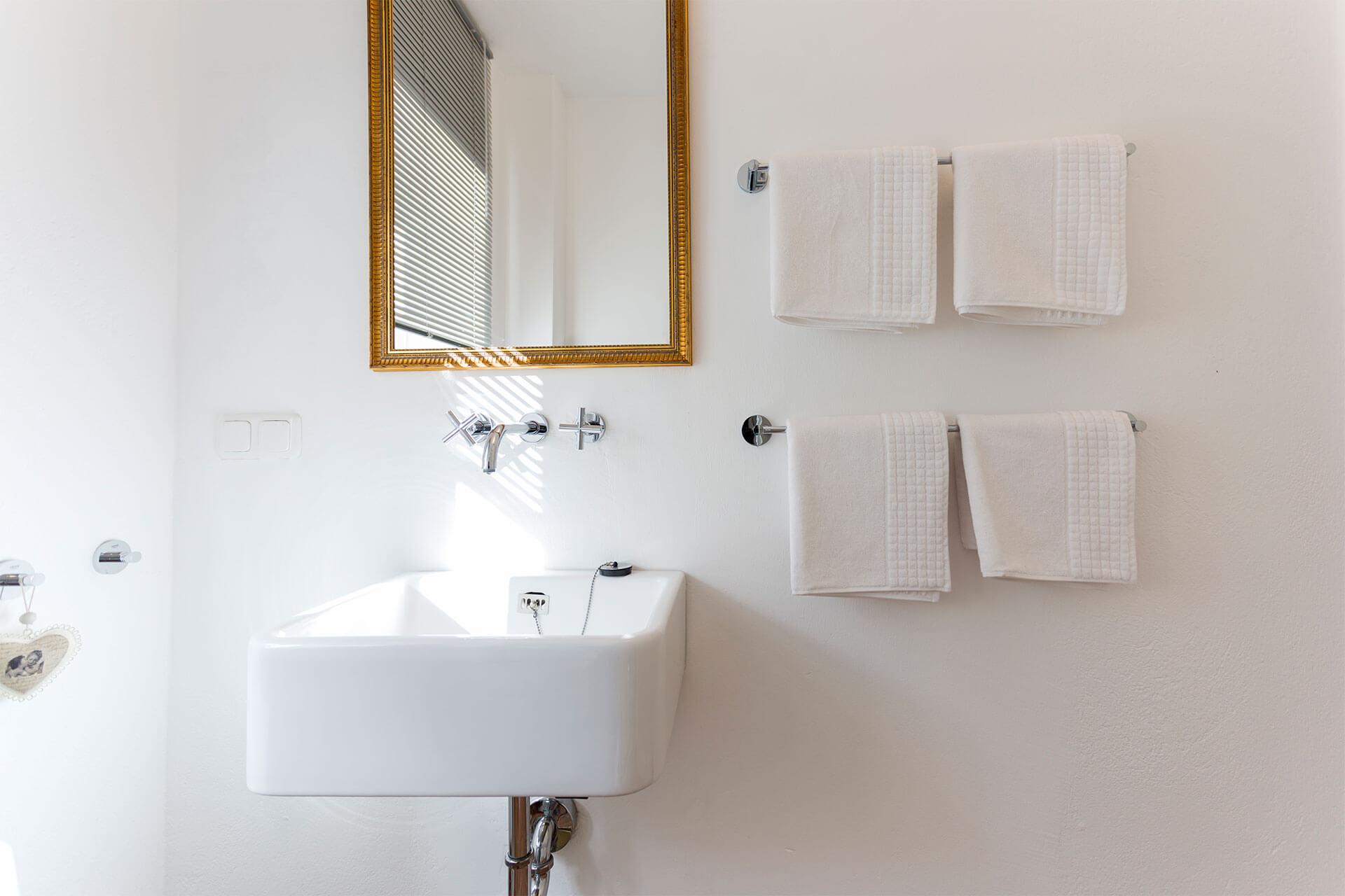 Armaturen am Waschbecken und frische aufgehängte Handtücher