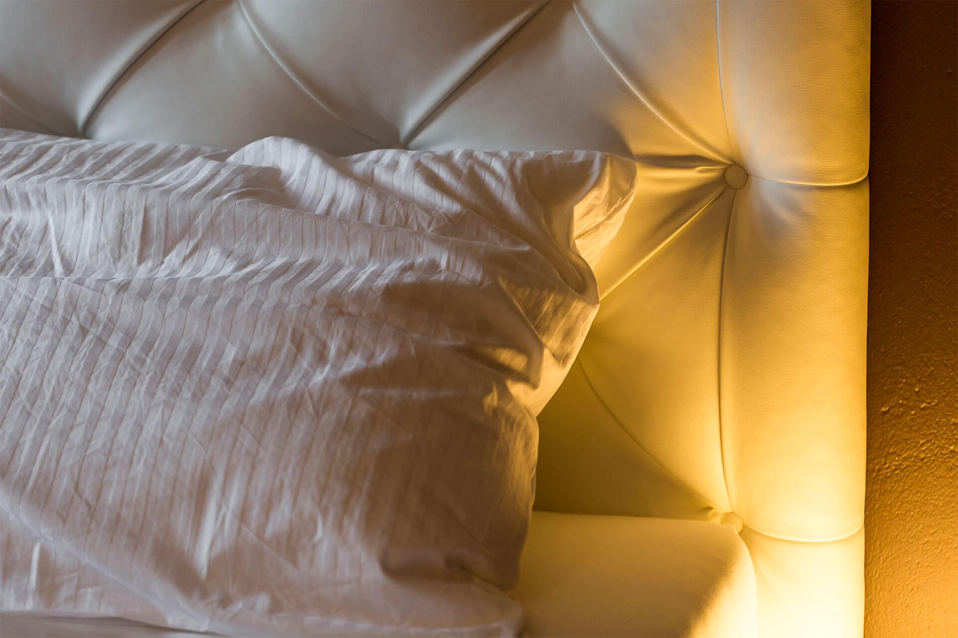 Kissen mit weißem Bezug auf dem Boxspring Bett
