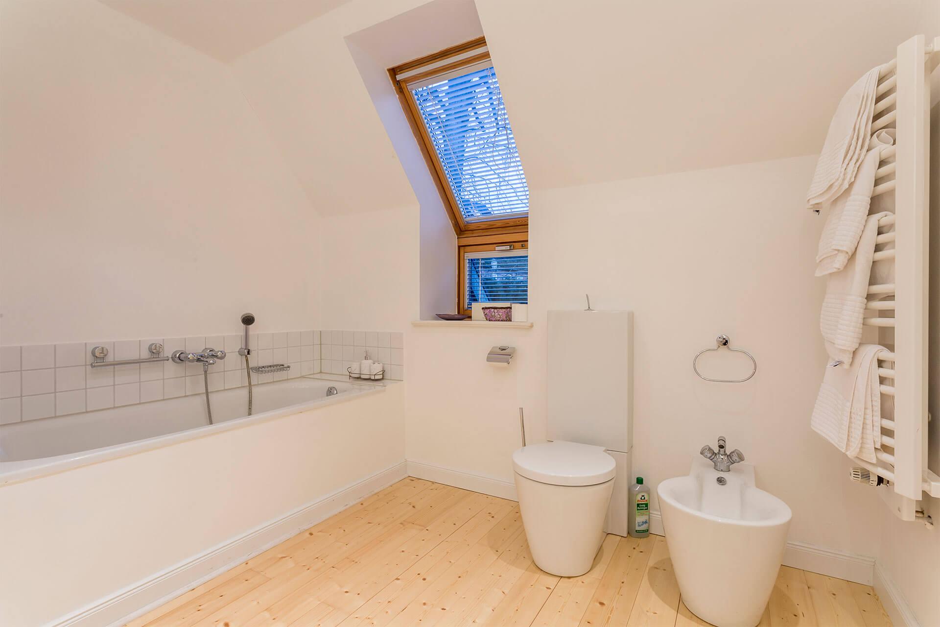 Badezimmer mit Badewanne, Bidet, Designer WC und Holzboden