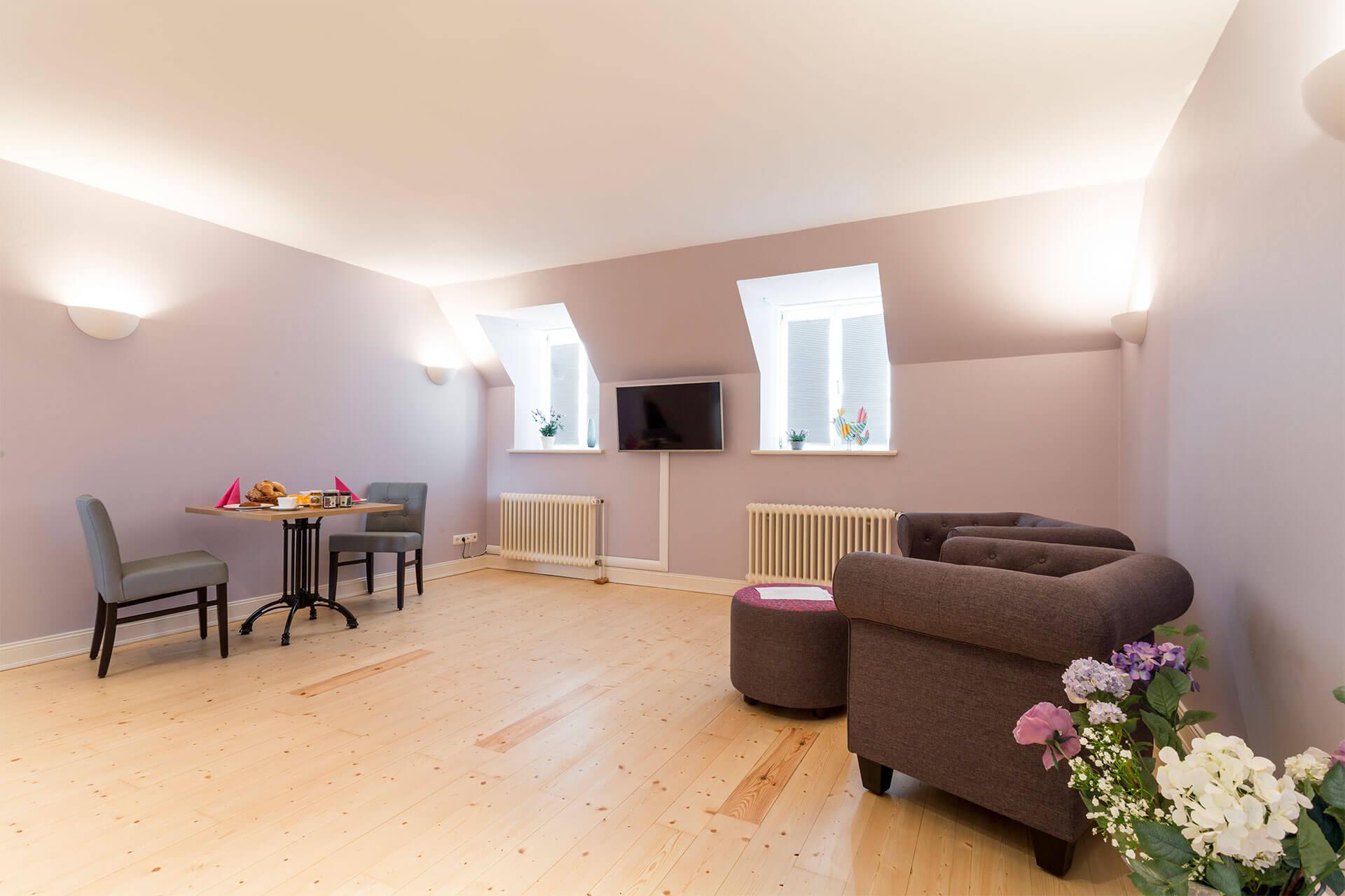 Der Wohnbereich mit Esstisch und Stühlen sowie Fernseher und Sesseln