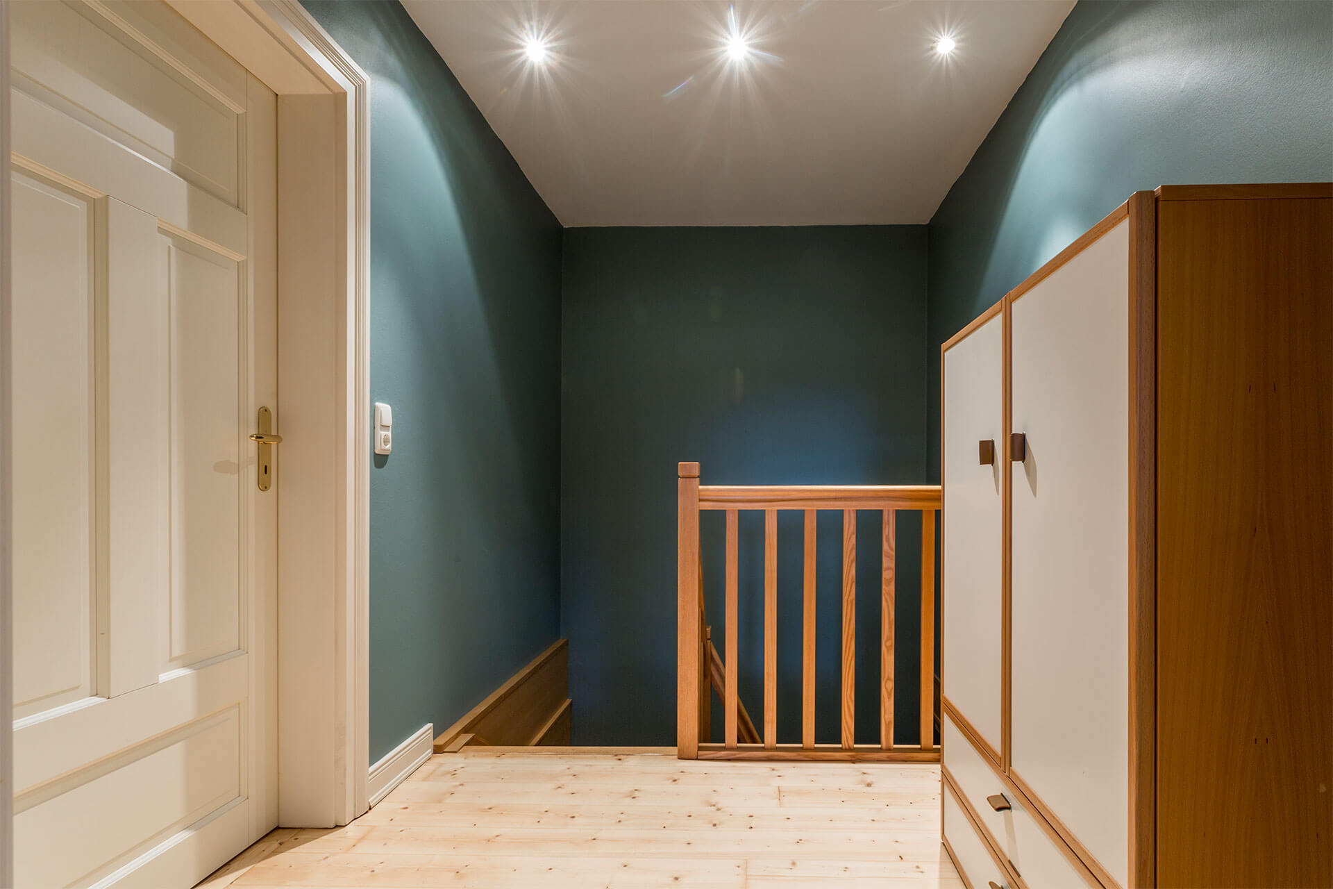 Der Flur mit Treppe nach unten und Tür zum Schlafzimmer. Ein Schrank.