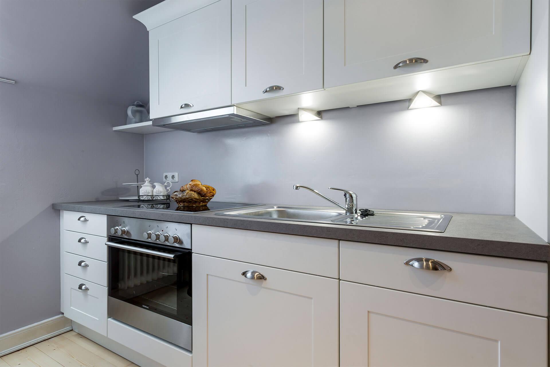 Eine weiße Landhausküche mit Ofen, Herd, Geschirrspüler