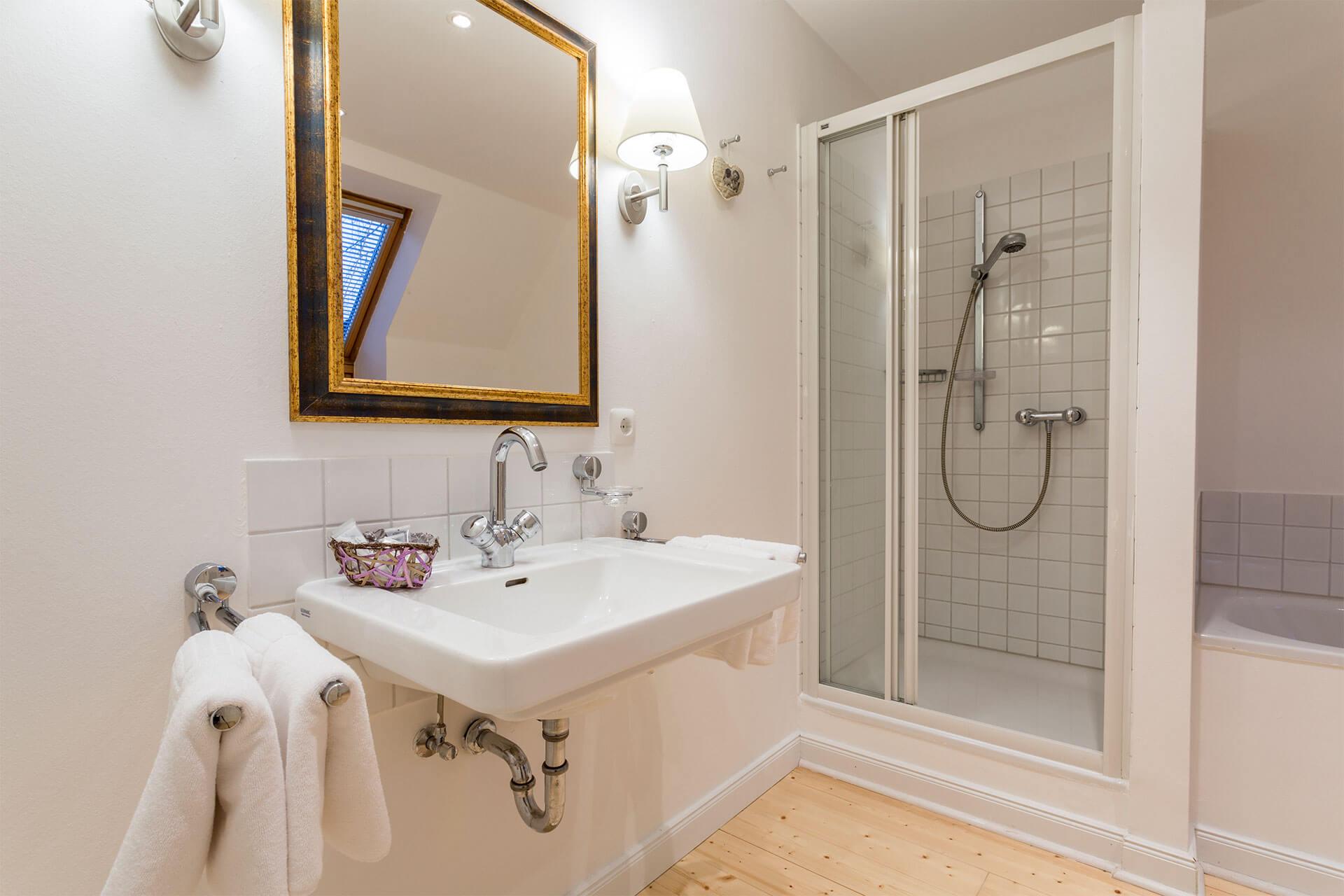 Dusche mit geöffneter Glaskabine und Spiegel über Waschbecken
