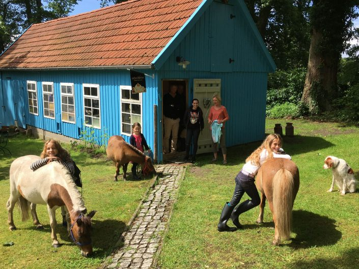 Guests and dog standing in front of the bar with ponies
