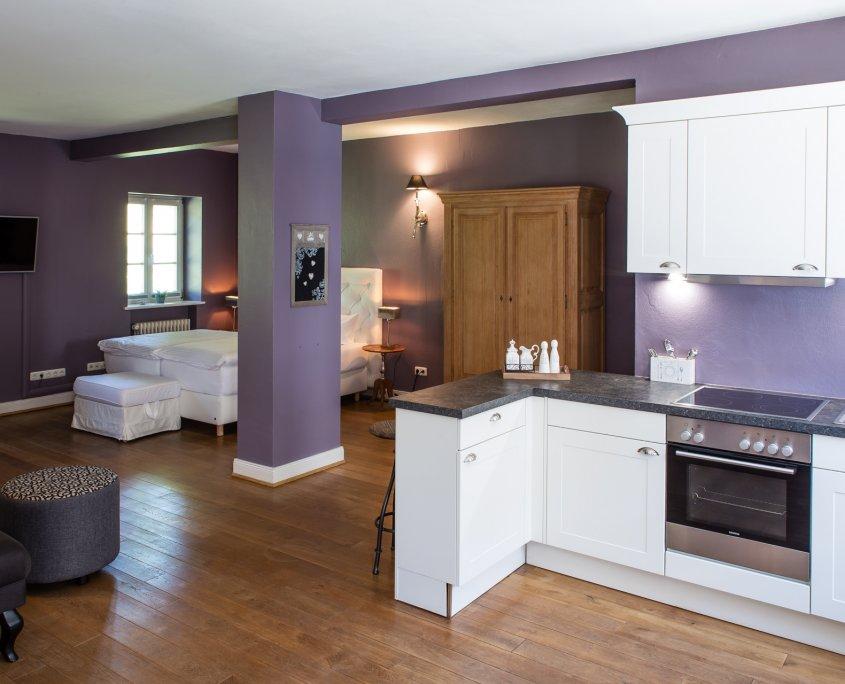 Teil der offenen weißen Küche mit Tresen und Hockern
