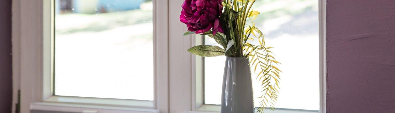 Vase mit Peonieen auf dem Fensterbrett
